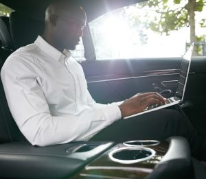 African businessman working on laptop inside a car